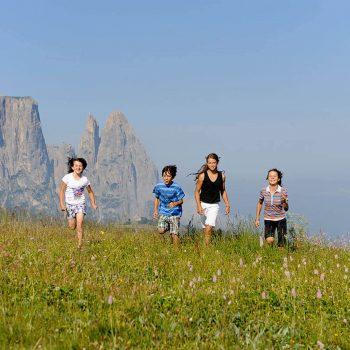 I bambini corrono su prati fioriti sull'Alpe di Siusi un paradiso escursionistico